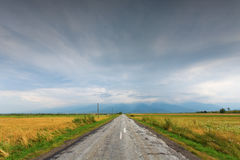 Country Road with blue rainy clouds Royalty Free Stock Image