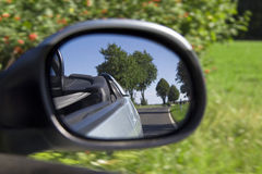 Country road in car side mirror Royalty Free Stock Image