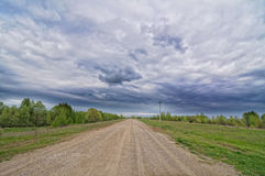 Country road with cloudy sky Stock Photography