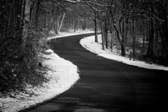 A country road curves uphill surrounded by snow in winter, black and white. Adventure, travel stock photography