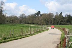 Country road delivery. Quiet farm road in the countryside with a delivery van Royalty Free Stock Photography
