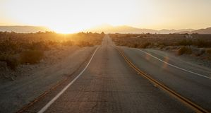 Country Road Through Desert Looking Towards Setting Sun On Horizon royalty free stock images