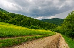 Country road down the hill through the field. Lovely countryside scenery in mountainous area before the summer storm Royalty Free Stock Photo