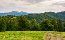 Country road down the hill in to the forest. Beautiful scenery of Carpathian nature. high mountain ridge in the distance Stock Photo