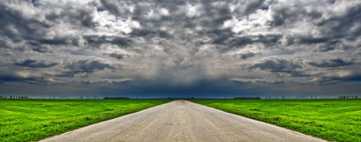 Country road and dramatic cloudy sky. Dramatic sky and country road in middle of green field Royalty Free Stock Photography