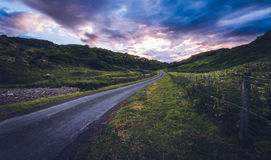 Country road at dusk. Deserted country road at dusk with dramatic clouds Royalty Free Stock Photography