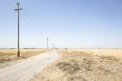 Country road with electricity pylons on a summer day Royalty Free Stock Image