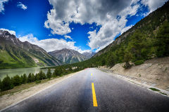 Country road at the european alps. Empty asphalt road with cloudy sky and sunlight Royalty Free Stock Photography