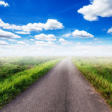 Country road  on field and blue sky Stock Image
