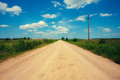 A country road through a field leading into the distance to infinity Royalty Free Stock Photo