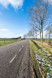Country road in a flat rural landscape Stock Photos