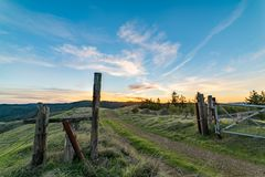 Country road going through fence with orange sunset at horizon stock images