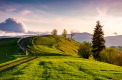 Country road through grassy hill at sunset. Lovely landscape in mountains under the ravishing evening sky with some fluffy clouds Stock Image