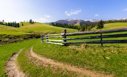 Country road through grassy rural hillside. Lovely springtime scenery in mountainous area stock images