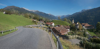 Country road through idyllic mountain village luzein, switzerlan Royalty Free Stock Photo