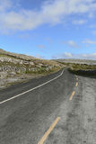 Country road intersects The Burren limestone karst landscape Royalty Free Stock Images