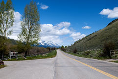 Country Road. In Jackson Hole, Wyoming with snowcapped mountains in the background Royalty Free Stock Photo