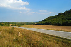 Country road landscape. Sunny day, blue sky royalty free stock image