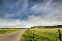 Country Road: Landscape. A long country road follows a beautiful green grassland under a dramatic cloudy blue sky Royalty Free Stock Photos