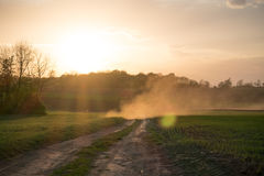 Country road landscape in sunset. Sun rays through the dust Stock Photography