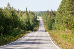 Country road in Lapland, Finland, on a sunny summer day Stock Photos