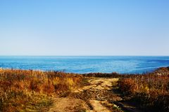 Rustic road to the seaside. The panorama of a blue sea stock image