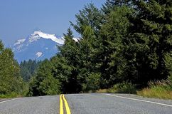 Country Road With Mountain In Background. This country road shows the double yellow lines of the highway with forest to the sides of the road and a beautiful Stock Photography