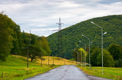 Country road in mountains. Lights and power line tower along the road Stock Photos