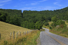 Country Road in the Mountains. A curve in a country mountain road in the summer stock images