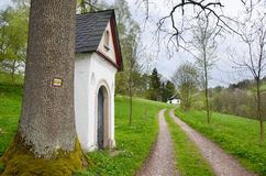 Country road in Orlic Mountains (Czech: Orlicke hory), Czech Republic. Country road with old chapel and tourist sign on a tree in the middle of Orlic Mountains Royalty Free Stock Photos