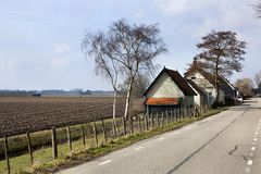 Country road and a plowed field in Dutch polder landscape Royalty Free Stock Photo