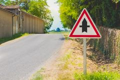 Country road with a priority crossroads sign royalty free stock images