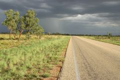 Country road before rain. Country road with few trees by the roadside and dark gray clouds over the sky. Kimberley, Western Australia, Australia Royalty Free Stock Photo