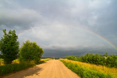Country road and rainbow Stock Image