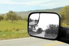 A country road. A rearview mirror depicts the past in black and white. A concept image Royalty Free Stock Image