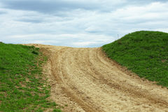 Country road is rising the horizon. On green field Stock Photo