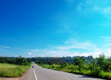 Country road rolls over hills and through a thick forest. Blue sky, royalty free stock image