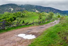 Country road through rural area in mountains. Beautiful landscape on a cloudy day in springtime Stock Photography