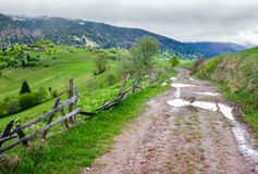 Country road through rural area in mountains. Beautiful landscape on a cloudy day in springtime Royalty Free Stock Photos