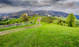 Country road through rural area in mountains. Beautiful springtime scenery on cloudy day stock photography