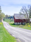 A country road and Rustic red barn in Michigan usa royalty free stock image