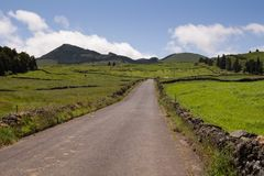 Country road, Sao Miguel, Azores Islands. Good quality of the asphalt country road, lined by fields, meadows and hills. Cloudy spring sky. North of Sao Miguel stock photo