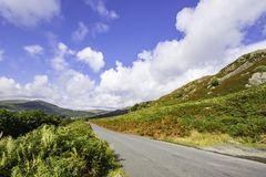 Country road with scenic view in Lake District,Cumbria,Uk. Country road with view on scenic mountain valley, blue sky with clouds and natural light painting on royalty free stock photography