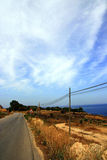 Country road on sea. A quiet road along the Sicilian coast in Italy. The sea is visible in the distance, and a sign warns of a turn in the road ahead Royalty Free Stock Image