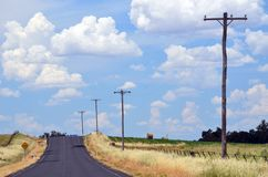 Summer heat haze on a country road through farmland. Country road shimmering in summer heat haze and lined by fields and telegraph poles near Canowindra in rural stock images