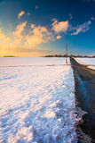 Country road and snow covered fields at sunset, in rural York Co Royalty Free Stock Photos