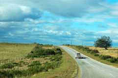 Country road South Africa. A lonely car with a trailer driving on an empty country road with tourists on vacation travelling in South Africa on a sunny summer Royalty Free Stock Photo