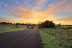 Country Road sunrise. Country road, farms and paddocks at sunrise morning.  Focus to foreground Stock Photography