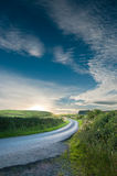 Country road at sunset. Curved track leading to a summer sunset in Scotland Stock Images