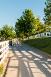 Country road surrounded the horse farms with evening fence shado Stock Photos